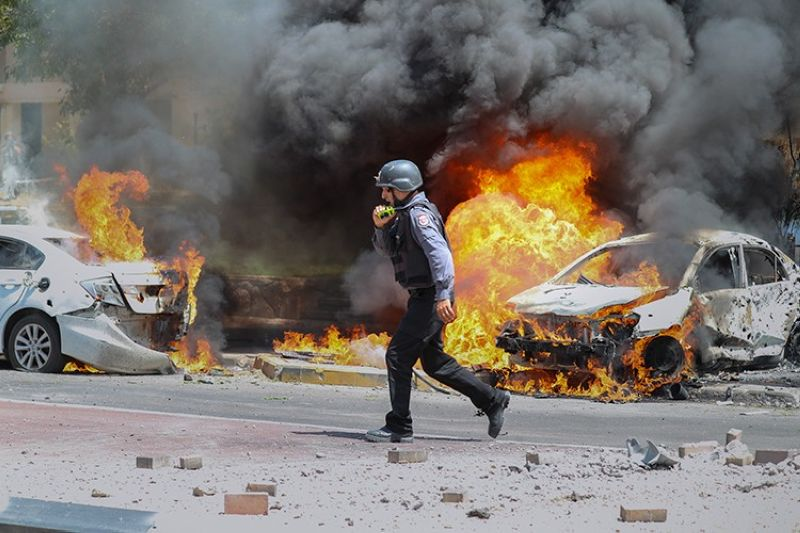ISRAEL. An Israeli firefighter walks next to cars hit by a missile fired from Gaza Strip, in the southern Israeli town of Ashkelon, Tuesday, May 11, 2021. (AP)
