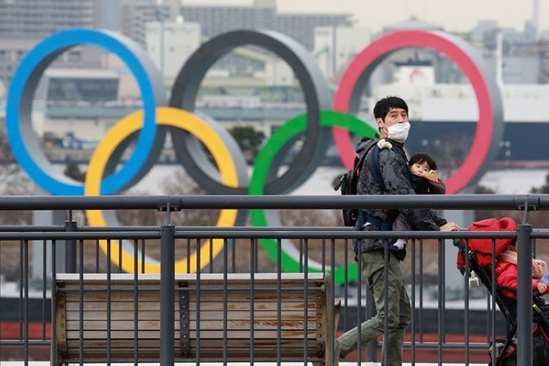 JAPAN. People wearing face masks to protect against the spread of the coronavirus walk on the Odaiba waterfront as Olympic rings is seen in the background in Tokyo, Tuesday, January 26, 2021. (AP)