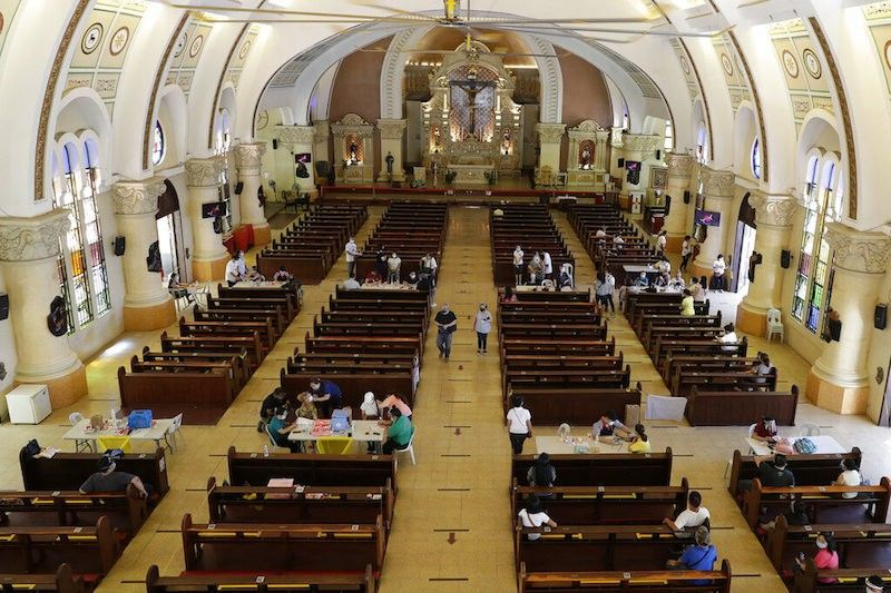 MANILA. Health workers inoculate residents with the AstraZeneca Covid-19 vaccine inside the Sacred Heart of Jesus Parish church in Quezon City on May 17, 2021. (AP)