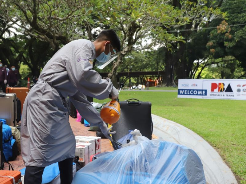 SAFETY PROTOCOL. In this file photo taken in September 2020, a hotel worker sanitizes bags and luggage of players and coaches upon their arrival at Clark, Pampanga for the PBA Bubble. (BCDA)