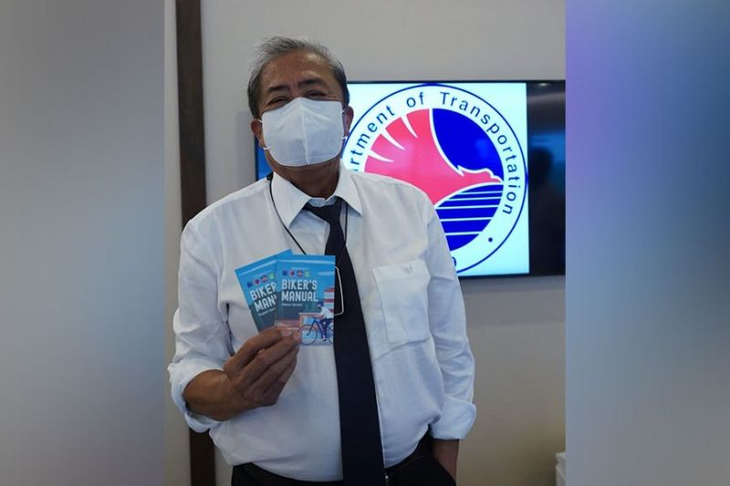 DOTr Secretary Arthur Tugade with the English and Filipino version of the DOTr-SM bike manual. The manual aims to promote safety, courtesy and etiquette on the road among cyclists, motorists, and pedestrians.