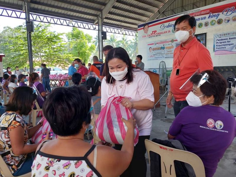 AID TO SOLO PARENTS. Board Member Mylyn Pineda-Cayabyan and Mayor Abundio Punsalan Jr. lead the distribution of grocery packs to Simonian solo parents. (Contributed photo)