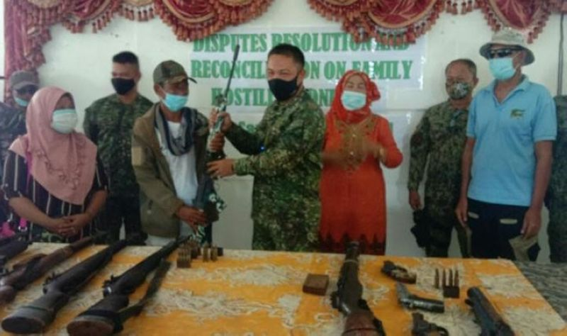 ZAMBOANGA. Two clans, whose dispute was triggered by boundary disagreement, sign a peace pact Friday, May 28, facilitated by the Joint Task Force-Tawi-Tawi in coordination with the police and local government officials. A photo handout shows a clan member surrenders a rifle to Lieutenant Colonel Venjie Pendon, Marine Battalion Landing Team-6 commander during the settlement ceremony. (SunStar Zamboanga)