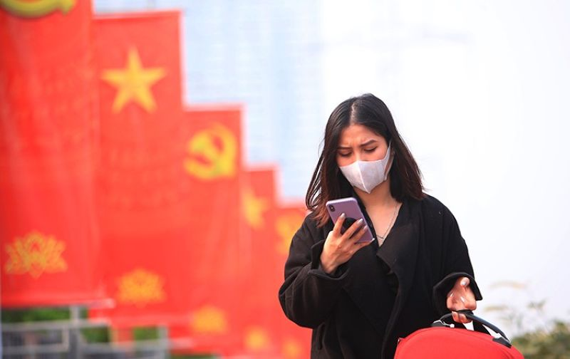 VIETNAM. In this January 23, 2021 file photo, a woman wearing face mask looks at her phone in Hanoi, Vietnam. (AP)