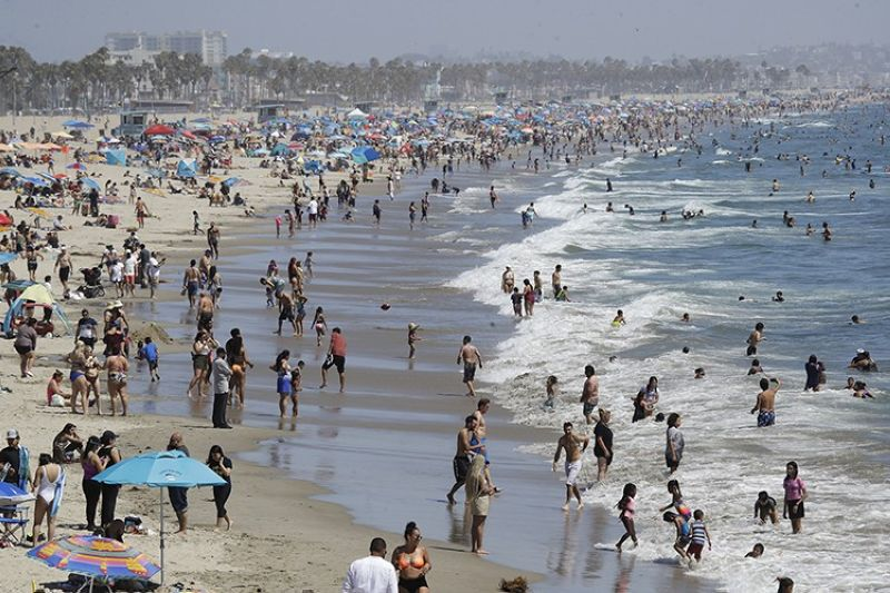 In this July 12, 2020, file photo, visitors crowd the beach in Santa Monica, Calif., amid the coronavirus pandemic. Californians headed to campgrounds, beaches and restaurants over the long holiday weekend as the state prepared to shed some of its coronavirus rules. (AP File Photo)