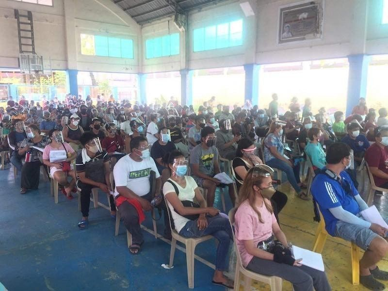 MANILA. Residents of Muntinlupa City queue for the cash assistance promised by the government in this photo taken in April 2021. (File)