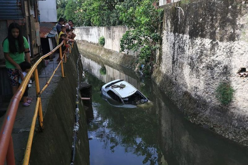 TAXING INCIDENT. A taxi is stuck in a creek in Sitio Paray, Barangay Kasambagan, Cebu City on Wednesday morning, June 2, 2021. As Tropical Storm Dante dumped rains, its driver had parked the taxi roadside near the creek to avoid a flooded area in Barangay Subangdaku, Mandaue City past 6 p.m. Tuesday, June 1. But the flood reached the taxi and swept it into the creek, carrying it to Paray. The driver was safe as he was able to get out of the taxi when it started to move. / ALAN TANGCAWAN