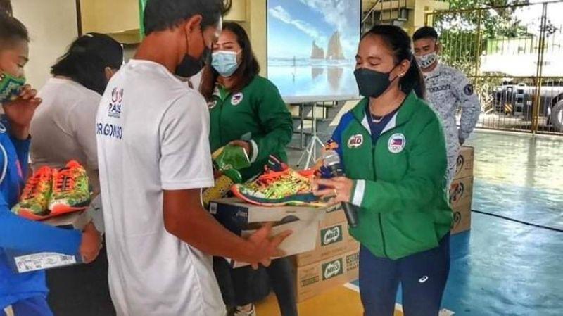 SAPATOS: Gitunol ni Olympian marathoner Mary Joy Tabal (tuo) sa usa ka batan-ong atleta ang usa sa 120 ka mga pares sa sapatos nga iyang gipanghatag sa mga miyembro sa Philippine Accessible Disability Services Inc. (PADS) kagahapon, Hunyo 4, 2021. / Tampo