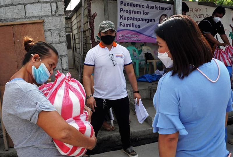 FOOD AID. Board Member Mylyn Pineda-Cayabyab talks to a beneficiary of the food aid program during the recent distribution of assistance in Barangay Panipuan. (Contributed photo)