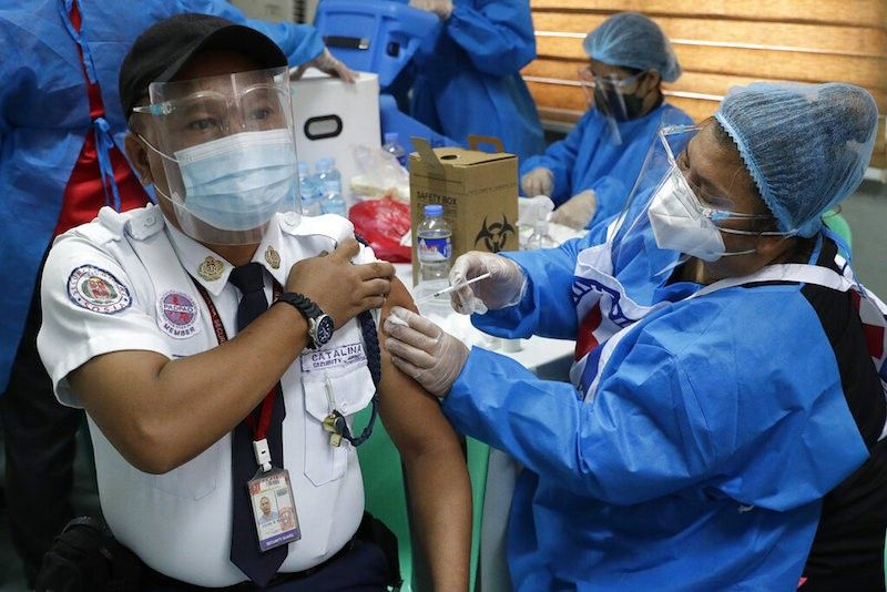 MANILA. Security guard Joenil Mibulos is inoculated with China's Sinovac Covid-19 vaccine at the Navotas Fish Port on June 7, 2021. (AP)