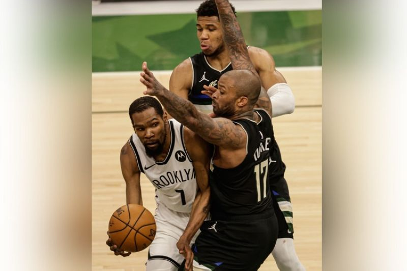 Brooklyn Nets' Kevin Durant (7) is guarded by Milwaukee Bucks forward P.J. Tucker (17) during the second half of Game 6 of a second-round NBA basketball playoff series Thursday, June 17, 2021, in Milwaukee. (AP Photo)