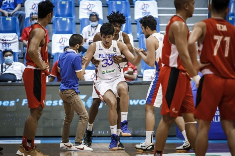 PAMPANGA. Cebuano forward Carl Tamayo is helped up by his teammates after spraining his ankle in the game versus Indonesia. (FIBA)