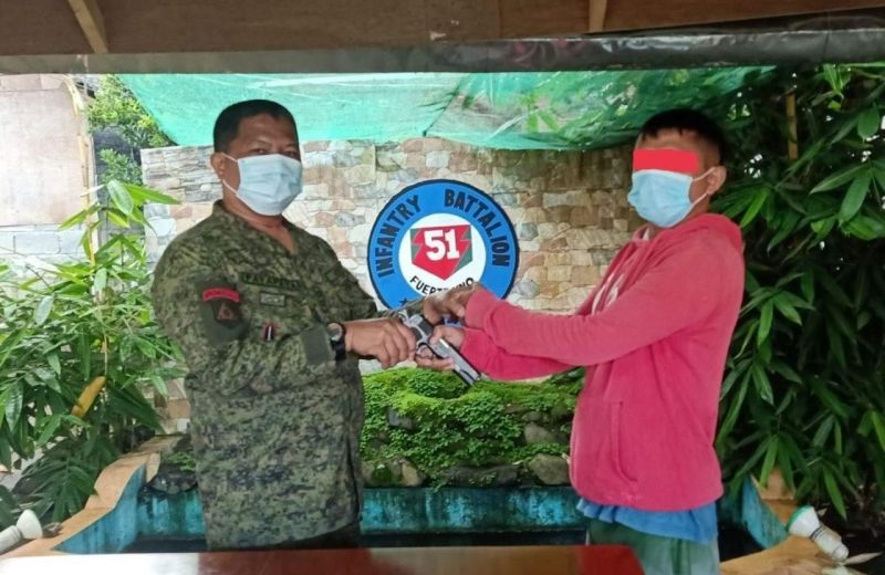 ZAMBOANGA. A ranking leader of the communist New People's Army (NPA) identified as Ka Nets (right) surrenders Thursday, June 17, to military authorities in Lanao del Sur. A photo handout shows Nets handing over a caliber .45 pistol to Lieutenant Colonel Fernando Payapaya, 51st Infantry Battalion commander (left) during his surrender. (SunStar Zamboanga)