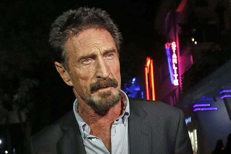 In this Dec. 12, 2012, file photo, anti-virus software founder John McAfee answers questions to reporters as he walks on Ocean Drive, in the South Beach area of Miami Beach, Fla. McAfee, the outlandish security software pioneer who tried to live life as a hedonistic outsider while running from a host of legal troubles, was found dead in his jail cell near Barcelona, Spain, on Wednesday, June 23, 2021. His death came just hours after a Spanish court announced that it had approved his extradition to the United States to face tax charges punishable by decades in prison, authorities said. (AP Photo/Alan Diaz, File)