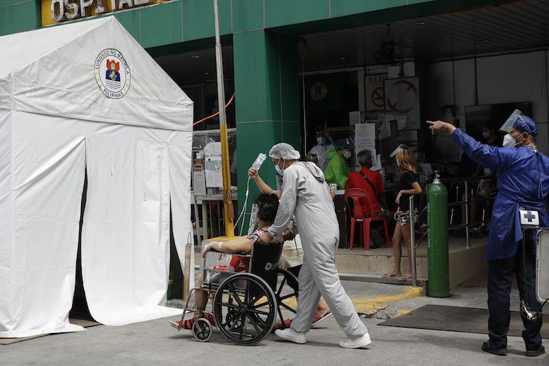 MANILA. A health worker wearing a protective suit pushes a COVID-19 patient to an isolation tent outside a hospital in Manila in this photo taken in April 2021. (File)