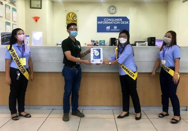 NEGROS: DTI-Negros Occidental Consumer Protection Unit Head Romel Amihan awards the Safety Seal to SM Supermarket personnel headed by store manager Ria Ablong at the mall in Bacolod City Thursday. (Contributed photo)