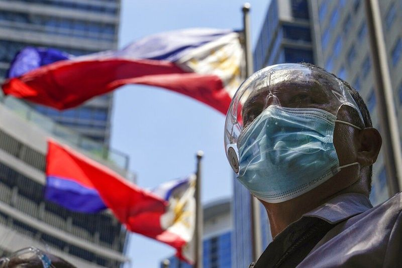 MANILA. A man wearing face mask and face shield to prevent the spread of the coronavirus stands beside Philippine flags in Taguig City on Saturday, June 18, 2021. (AP)
