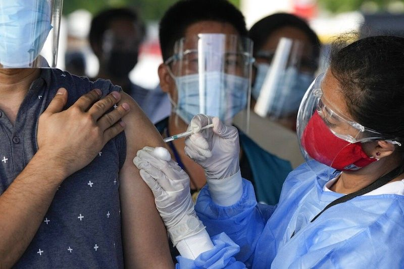 MANILA. A health worker inoculates a man with China's Sinovac Covid-19 vaccine at a temporary vaccination center in Manila on June 22, 2021. (AP)