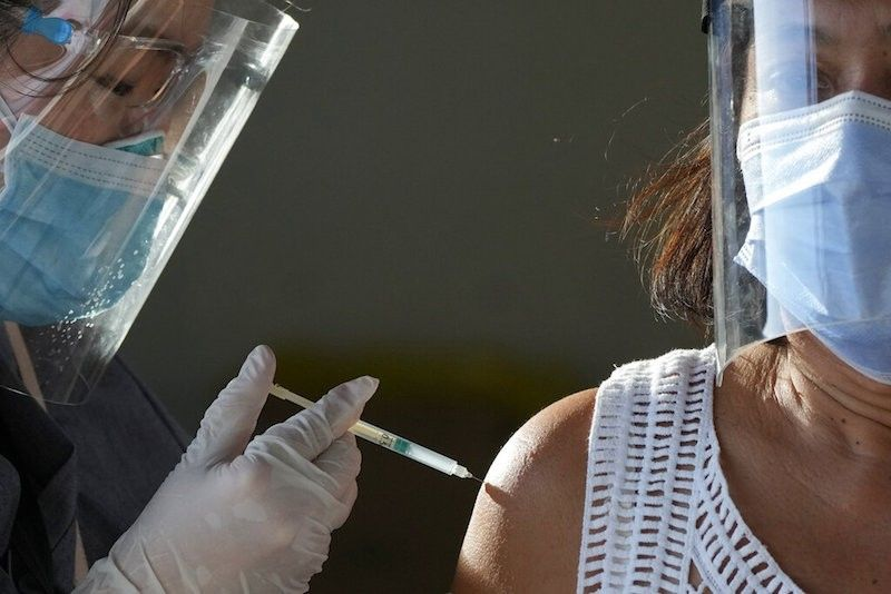 A health worker inoculates a woman with China's Sinovac Covid-19 vaccine at a temporary vaccination center in Manila on June 22, 2021. (AP)