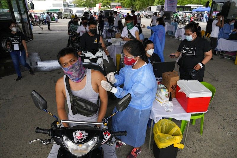 MANILA. A motorcycle rider is inoculated with China's Sinovac Covid-19 vaccine at a drive-thru vaccination center in Manila on June 22, 2021. (AP)