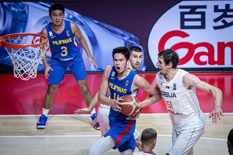 Kai Sotto drives around the defense of Serbia's Bojan Marjanovic. (FIBA)
