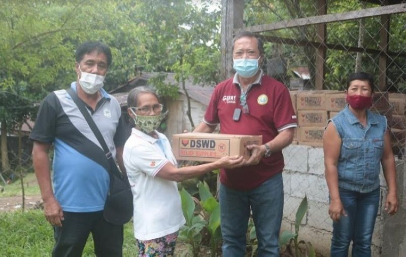 MURCIA. Mayor Gerry Rojas, with Canlandog Punong Barangay Reynaldo Gawan and Purok President Gina Gibara, gives a food pack to a resident of Sitio Monark, Barangay Canlandog. (PR)