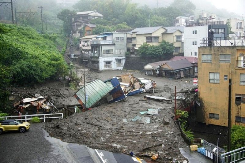 JAPAN. Houses are damaged by mudslide following heavy rain at Izusan district in Atami, west of Tokyo, Saturday, July 3, 2021. A powerful mudslide carrying a deluge of black water and debris crashed into rows of houses in a town west of Tokyo following heavy rains on Saturday, leaving multiple people missing, officials said. (Naoya Osato/Kyodo News via AP)