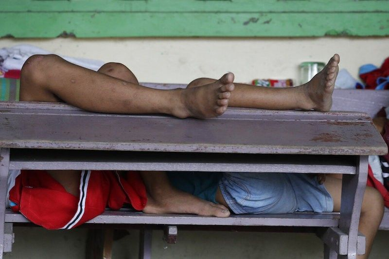 BATANGAS. Young boys who fled their homes sleep on school desks at a public elementary school turned evacuation center in Laurel town, Batangas on Friday July 2, 2021. (AP)