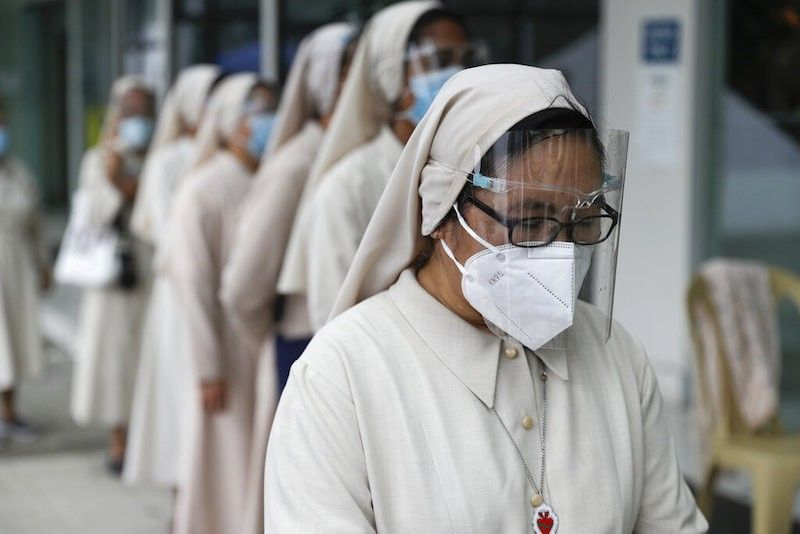 MANILA. In this photo taken on June 25, 2021, Catholic nuns wear face masks and face shields as they line up to to take a look at the urn containing the remains of former President Benigno S.C. Aquino III. (AP)