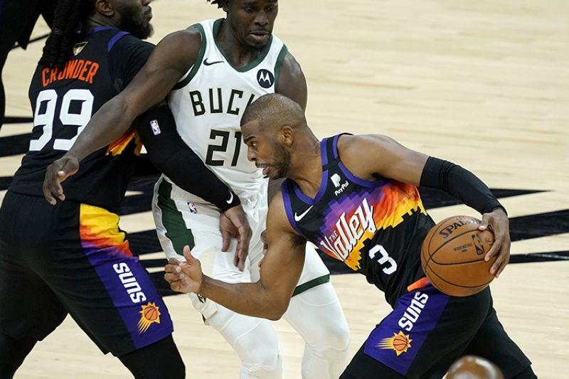 Phoenix Suns guard Chris Paul (3) drives past Milwaukee Bucks guard Jrue Holiday (21) during the second half of Game 1 of basketball's NBA Finals, Tuesday, July 6, 2021, in Phoenix. (AP Photo/Matt York)