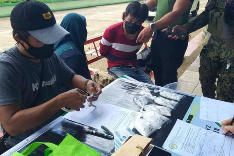 ZAMBOANGA. Joint police and Philippine Drug Enforcement Agency operatives arrest Jamael Omar (3rd from left, seated) and Salimah Amer (2nd from left) and seize some P3.4 million worth of illegal drugs in an anti-drug operation Thursday, July 8, in Zamboanga del Sur. A photo handout shows members of the arresting team conducting inventory on the pieces of evidences they recover from the two suspects. (SunStar Zamboanga)
