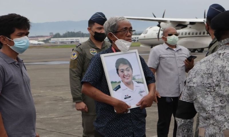 NOW HOME. Retired Col. Wilfredo Barrera Tato, 70, father of 1LT Sheena Alexandrea Tato - the female military nurse who died in the recent C-130 crash in Patikul, Sulu - is embracing his daughter's framed picture while the remains of Sheena were being unloaded from the plane on Friday at the Davao Air Station, Headquarters Tactical Operations Wing Eastern Mindanao (TowEastmin), Brgy. Sasa, Davao City.  TOWEASTMIN PIO