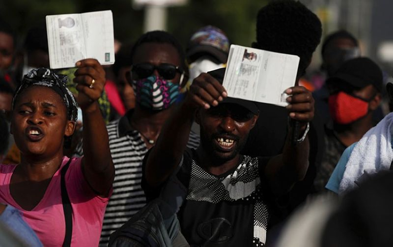 Haitians wave their passports shouting