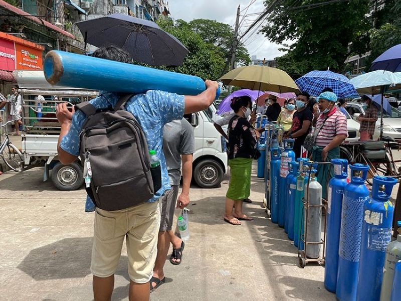 MYANMAR. A man carries an oxygen tank while others line up with their oxygen tanks outside an oxygen refill station in Pazundaung township in Yangon, Myanmar, Sunday, July 11, 2021. (AP)