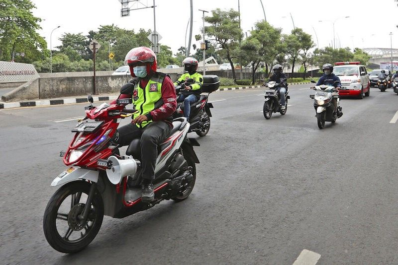INDONESIA. Motorcycle volunteers escort an ambulance carrying the body of a Covid-19 victim on its way to a cemetery for burial, in Bekasi on the outskirts of Jakarta, Indonesia on July 11, 2021. (AP)