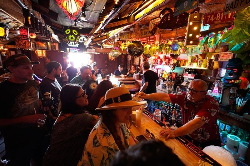 USA. In this July 7, 2021 file photo, patrons enjoy cold tropical cocktails in the tiny interior of the Tiki-Ti bar as it reopens on Sunset Boulevard in Los Angeles. (AP)