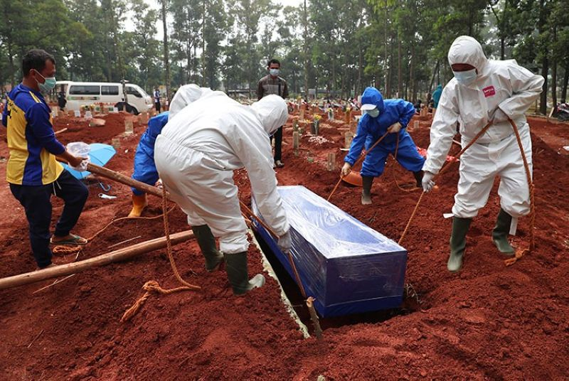 INDONESIA. Workers in protective gear lower a coffin of a Covid-19 victim to a grave for burial at the Cipenjo Cemetery in Bogor, West Java, Indonesia, Wednesday, July 14, 2021. (AP)