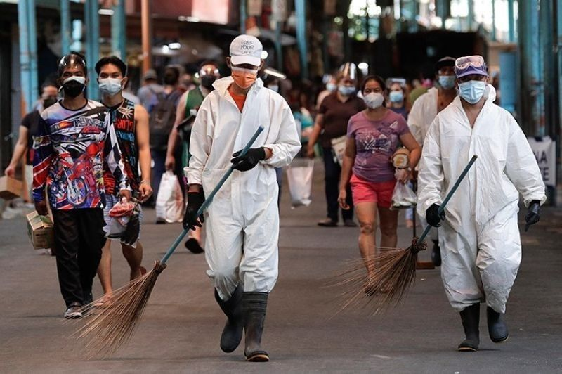 MANILA. Workers wearing protective suits walks beside residents at a public market during the start of a stricter lockdown to help prevent the spread of the coronavirus in Marikina City, Philippines on Monday, March 29, 2021. (AP)