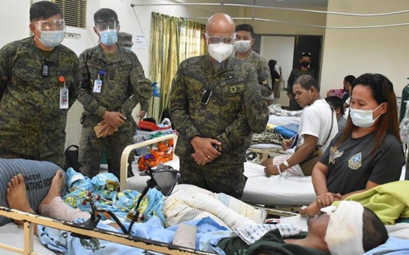ZAMBOANGA. Lieutenant General Corleto Vinluan, Jr., commander of the Western Mindanao Command (Westmincom) (standing, right), encourages the survivors of the July 4 C-130 plane crash to remain strong as they undergo healing process when he led the distribution Friday, July 16, of bundles of goodies the Armed Forces of the Philippines (AFP) Officers' Ladies Club donated to the victims. Assisting Vinluan is Navy Captain Robeline Carpio (left), Westmincom's assistant chief of Unified Command Staff for Personnel, and other Westmincom officials. (SunStar Zamboanga)