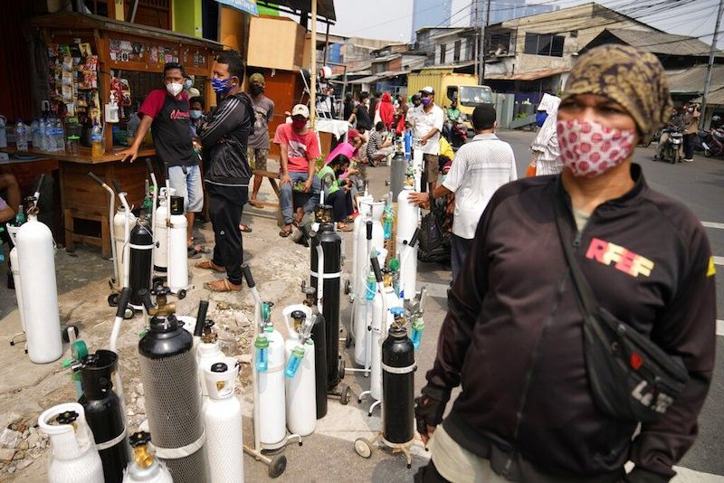 INDONESIA. People queue up to refill their oxygen tanks at a charging station in Jakarta, Indonesia on July 5, 2021. (AP)
