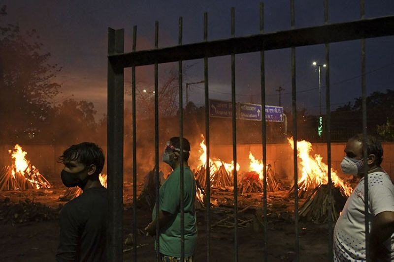In this May 6, 2021, file photo, people watch burning funeral pyres of their relatives who died of Covid-19 in a ground that has been converted into a crematorium in New Delhi, India. India's excess deaths during the pandemic could be a staggering 10 times the official Covid-19 toll, likely making it modern India's worst human tragedy, according to the most comprehensive research yet on the ravages of the virus in the south Asian country. (AP Photo/Ishant Chauhan, File)