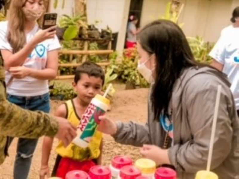 DAVAO. JCI Davaoeño Daba-Daba president Angel Angliongto hands out plastic tumblers to children at the Makilala housing project. (Contributed photo)