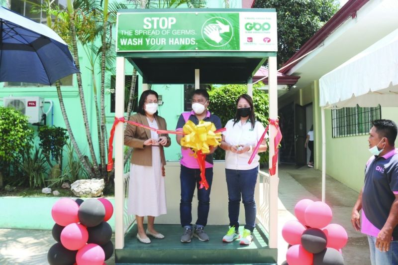 """CEREMONY. Cutting the ceremonial ribbon for the Toledo City Health Office handwashing station are (from left) Toledo City Mayor Marjorie """"Joie"""" Perales, City Health Officer Dr. Bonito Zanoria, and Leah Diaz, first vice president-Cebu operations of Global Business Power Corp. / CONTRIBUTED"""