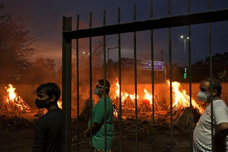 INDIA. In this May 6, 2021 file photo, people watch burning funeral pyres of their relatives who died of Covid-19 in a ground that has been converted into a crematorium in New Delhi, India. (AP)