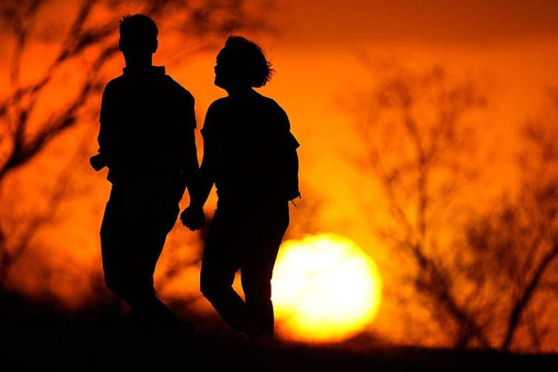 USA. In this March 10, 2021 file photo, a couple walks through a park at sunset in Kansas City, Missouri. (AP)