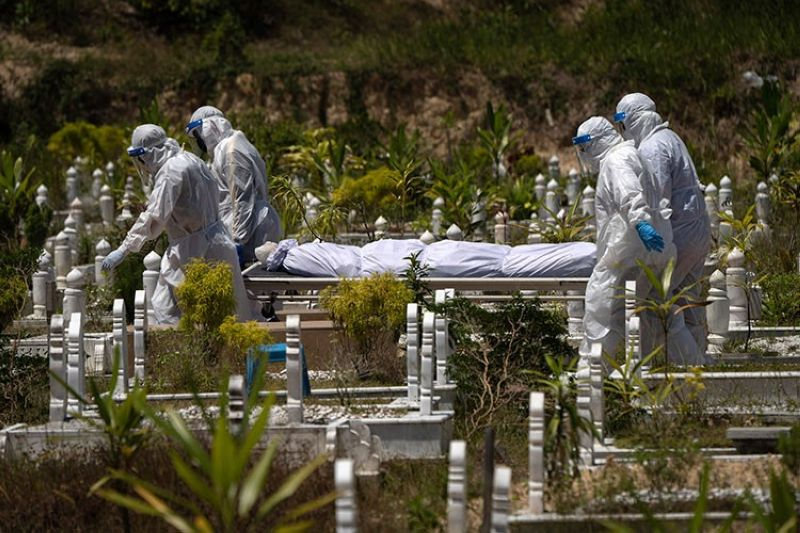 MALAYSIA. In this February 5, 2021 file photo, workers wearing personal protective equipment (PPE) carry the body of a victim of the coronavirus disease at a Muslim cemetery in Gombak on the outskirts of Kuala Lumpur, Malaysia. (AP)