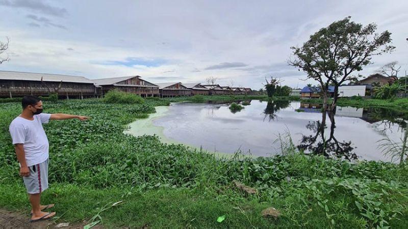 PAMPANGA. Neri De Leon, a resident of Barangay Sta. Monica, San Simon, Pampanga, points to a flooded portion along Quezon road due to clogged canals. (Chris Navarro)