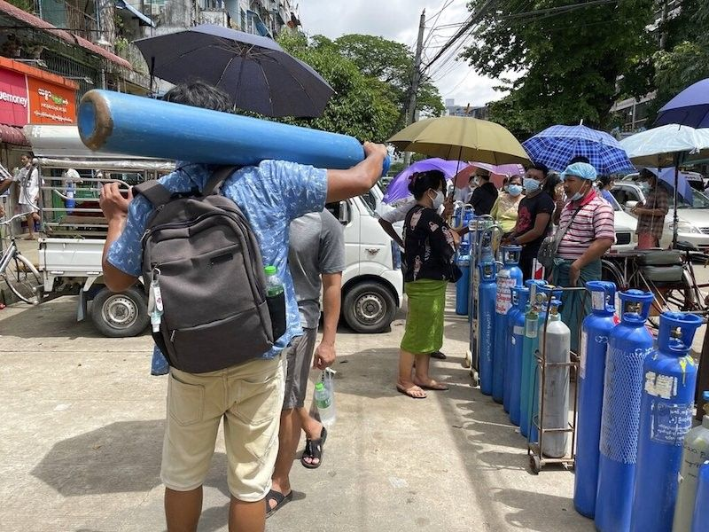 MYANMAR. A man carries an oxygen tank while others line up with their oxygen tanks outside an oxygen refill station in Pazundaung township in Yangon, Myanmar on July 11, 2021. Myanmar is facing a rapid rise in Covid-19 cases, which have caused a shortage in oxygen supplies. (AP)