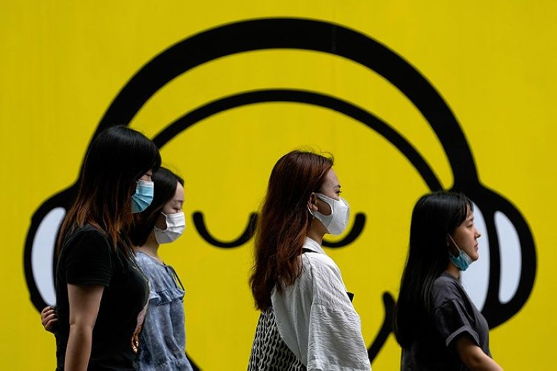 CHINA. Women wearing face masks to help curb the spread of the coronavirus walk by a smiley faces billboard during their lunch break in Beijing, Monday, July 19, 2021. (AP)
