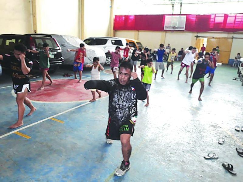 "SPORTS PROGRAM: Si Brgy. Day-as councilor ug Yaw-Yan Ardigma Cebu head Benigno ""Master Ekin"" Caniga Jr. (atubangan) nagtudlo og martial arts sa kabatan-unan sa sports summer program sa Brgy. Day-as. / Tampo"